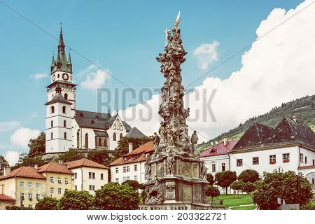 Saint Catherine's church and Plague column in Kremnica city Slovak republic. Architectural theme. Yellow photo filter.
