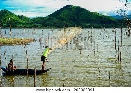 Kanchanaburi Thailand - July 14 2012: Fishermen on boat casting fishing net to catch fish in swamp in rural of Thailand