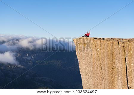 Preikistolen - amazing rock in Norway. Guy sitting on a cliff above the clouds. Pulpit Rock, the most famous tourist attraction in Ryfylke, towers over the Lysefjord