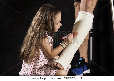 A little girl drawning a heart on plaster cast of her father