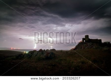 Enisala Medieval Fortress also referred as Heracleea Fortress on stormy weather,  with Razim lake in the background in Tulcea county, Dobrogea region, Romania