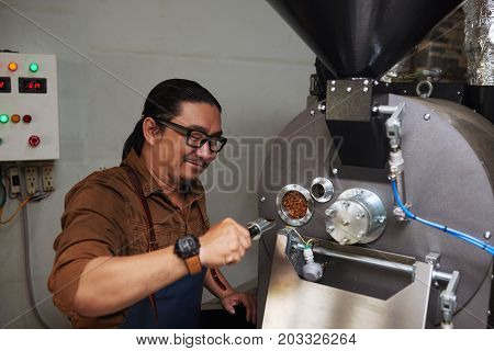 Barrista using modern roaster to prepare coffee beans