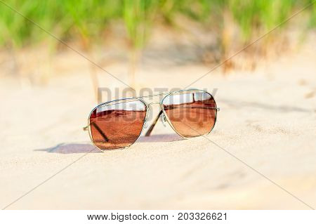 Trendy sunglasses with reflection lost on the beach sand. Multicolored outdoors closeup image.