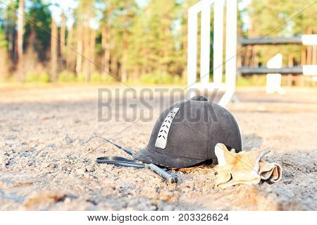 Equestrian equipment - helmet gloves and whip forgotten on the ground. Outdoors close-up.
