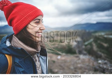 close up portret of Girl in warm clothing observing surroundings on background of mountains of Iceland.