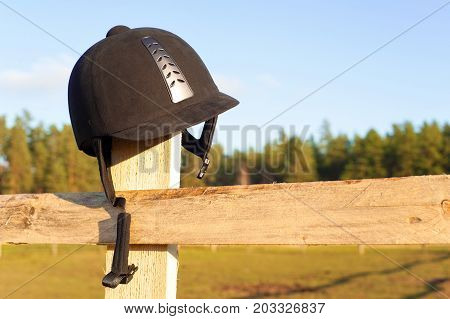 Equestrian equipment - forgotten helmet hanging on the wooden fence with blue sky background. Multicolored summertime outdoors horizontal close-up image.
