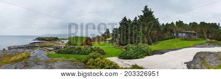 Stavanger Norway - August 28 2017: Panoramic view of wooden houses on the stony shore in Flor and Flaere garden in inclement weather