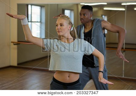 Female dancer with friend rehearsing against mirror at studio