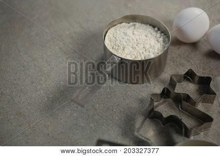 High angle view of flour in container with egg and pastry cutters on table