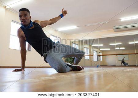 Male dancer rehearsing on hardwood floor at studio