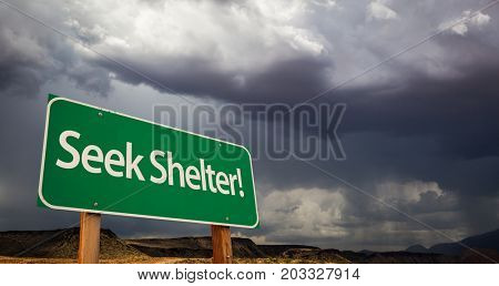 Seek Shelter Green Road Sign with Dramatic Clouds and Rain.