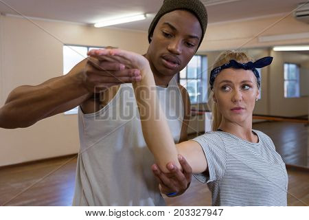 Young man assisting female friend in dance against mirror on floor