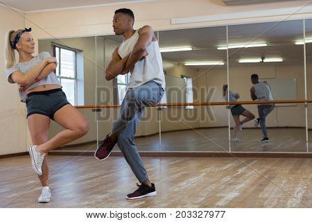 Full length of friends practicing dance against mirror on floor at studio