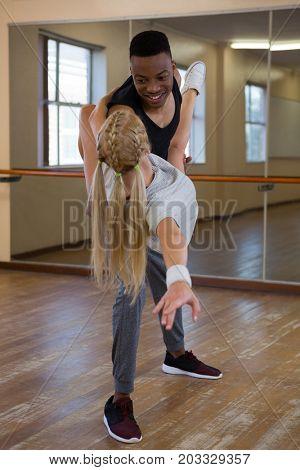 Man looking at female friend while dancing on hardwood floor at studio