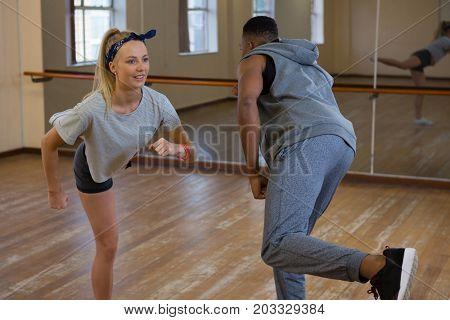 Friends rehearsing dance against mirror on wooden floor at studio