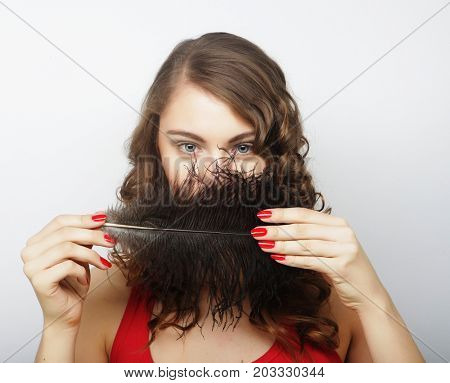Beautiful curly girl holding a black feather
