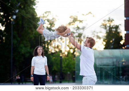 Young family on walk. The father cheerfully plays with the little daughter. He throws up his baby. Mother stands and smiles.