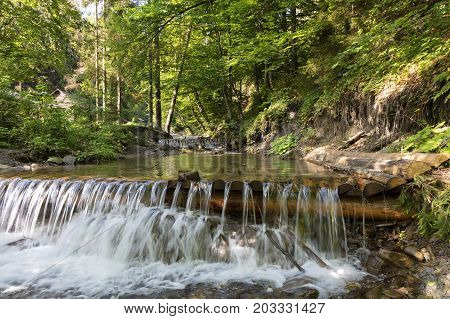 Daylight in the forest illuminates the clear waters of a mountain river. In the cascading waterfall of a mountain stream in the Carpathians the blue sky reflects.