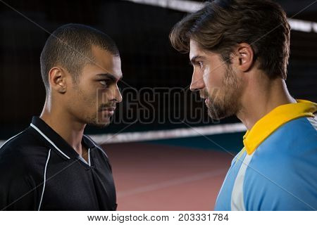 Aggressive male volleyball players looking each other at court