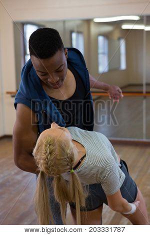 Young friends dancing on floor in studio