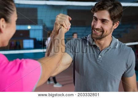 Determined volleyball player holding hand with female teammate at court