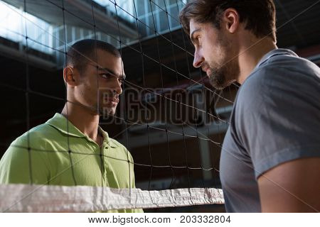 Aggressive male volleyball players looking at each other through net