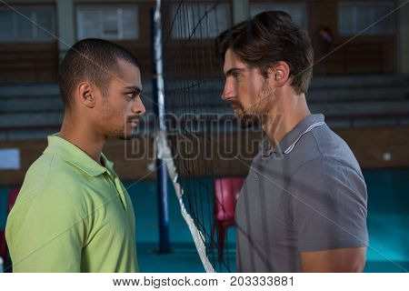 Side view of aggressive male volleyball players looking each other through net at court