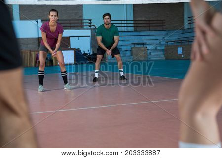 Full length of focused players practicing volleyball at court