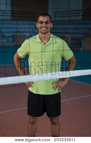 Portrait of smiling male volleyball player behind net standing at court