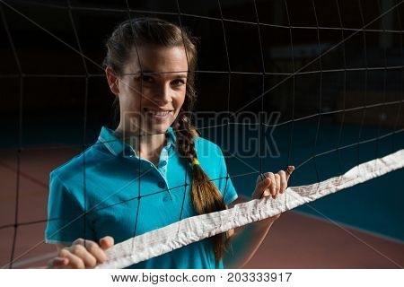 Portrait of female volleyball player standing by net at court