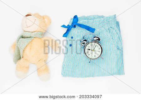 Plush Toy, Pajama Pants And Alarm Clock View From Above On A White Background