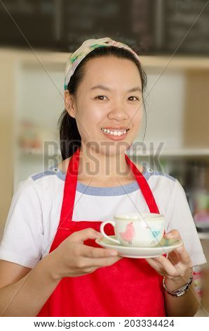 Asian woman barista holding a cup of coffee in the coffee shop