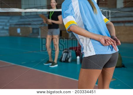 Mid section of female volleyball player gesturing while playing at court