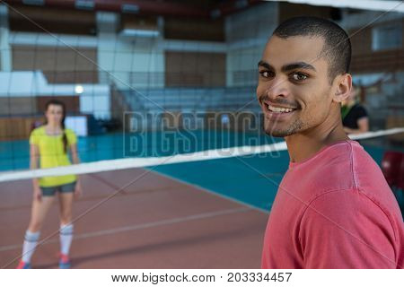 Portrait of smiling male volleyball player standing at court