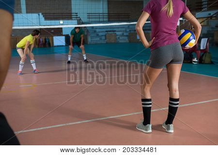 Low section of female volleyball player with team holding ball at court