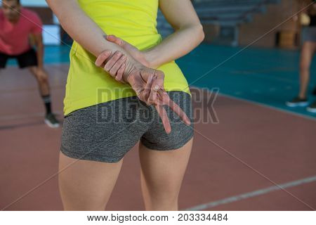 Mid section of volleyball player making strategy by gesturing at court