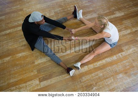 High angle view of dancers holding hands while sitting on wooden floor in studio