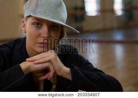 Portrait of young female dancer wearing cap on floor in studio