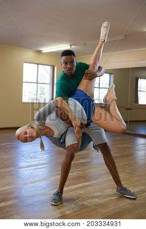 Portrait of young man carrying female friend on wooden floor in dance studio