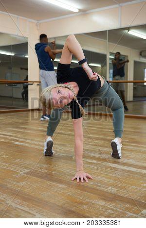 Portrait of young female dancer practicing on hardwood floor in studio