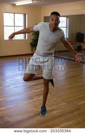 Full length portrait of male dancer rehearsing on wooden floor in studio