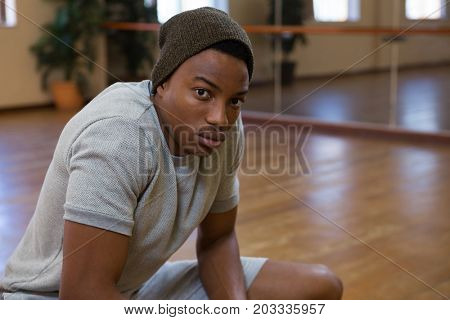 Portrait of male dancer crouching on wooden floor in studio