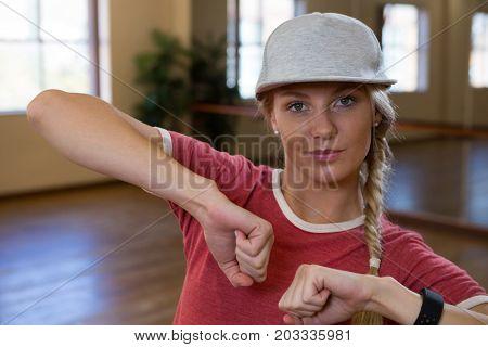 Portrait of young woman practicing dance on floor in studio