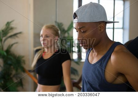 Thoughtful male dancer with friend by mirror in studio