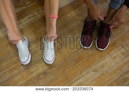 Low section of dancers tying shoelaces on wooden floor at studio