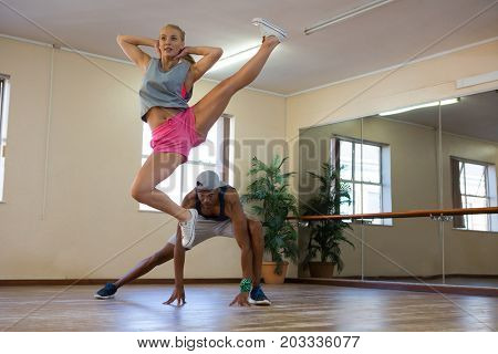 Full length of female dancer with young friend jumping in studio