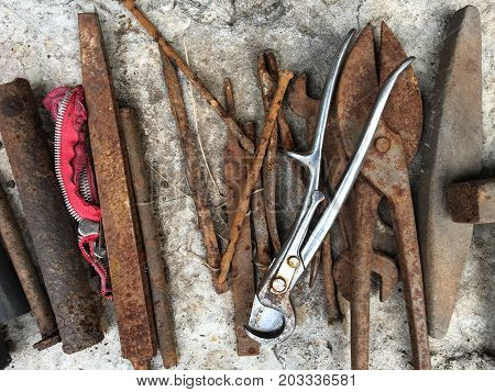 Old rusted tools over concrete, top view