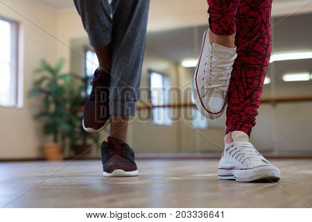 Low section of friends practicing dance on wooden floor