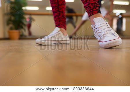 Low section of woman dancing on wooden floor in studio