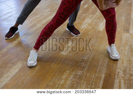 Low section of friends rehearsing dance on hardwood floor in studio